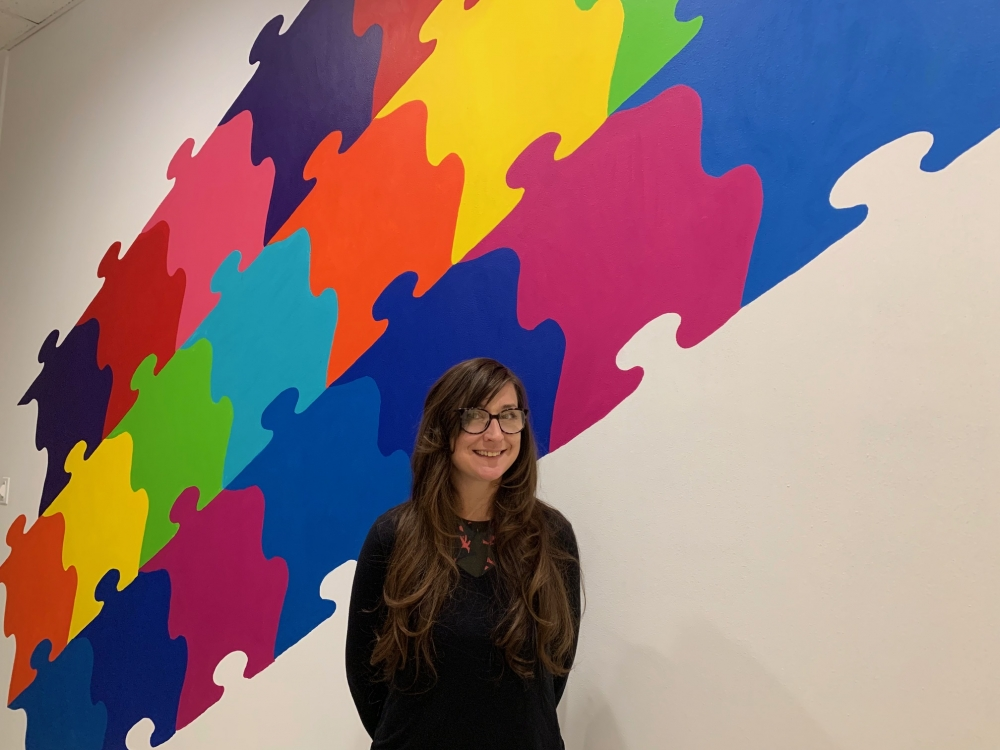 Local artist Kristin Brandt with the Puzzelation mural